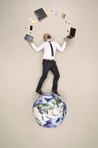 Businessman standing on globe juggling with office devicesの写真素材 [FYI04335320]
