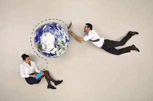 Business colleagues communicating around the globe via mobilの写真素材 [FYI04335322]