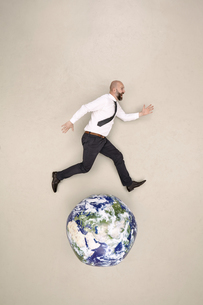 Businessman running on globeの写真素材 [FYI04335326]