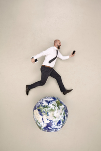 Businessman running on globe with mobile devicesの写真素材 [FYI04335328]