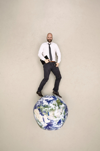 Businessman standing on globe with mobile devicesの写真素材 [FYI04335331]