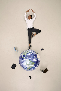Businesswoman doing a pirouette on globe with mobile devicesの写真素材 [FYI04335332]