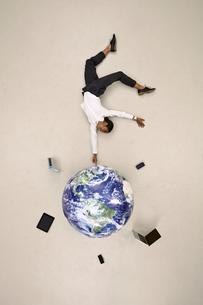 Businesswoman balancing on fingertip on globe with mobile deの写真素材 [FYI04335333]