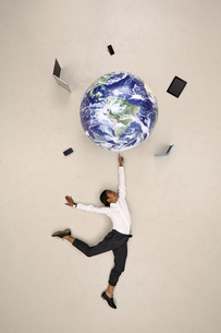Businesswoman balancing globe with mobile devices on fingertの写真素材 [FYI04335334]