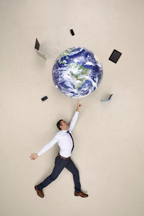 Businessman balancing globe with mobile devices on fingertipの写真素材 [FYI04335335]