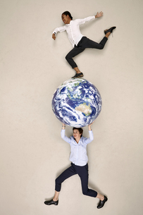 Businesswoman carrying globe with colleague on topの写真素材 [FYI04335340]