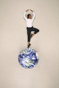Businesswoman doing a pirouette on globeの写真素材 [FYI04335341]