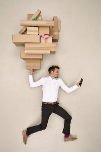 Businessman balancing cardboard boxes and looking on smartphの写真素材 [FYI04335342]
