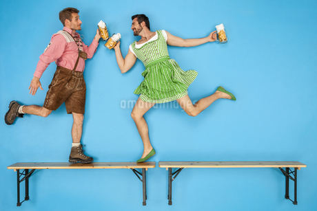 Gay couple at the Oktoberfest dancing on beer benchesの写真素材 [FYI04335344]