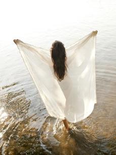 Germany, Brandenburg, Young woman holding transparent clothの写真素材 [FYI04335369]