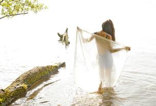 Germany, Brandenburg, Young woman holding transparent clothの写真素材 [FYI04335370]