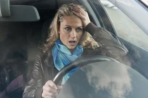 Germany, Brandenburg, Stress woman in carの写真素材 [FYI04335376]