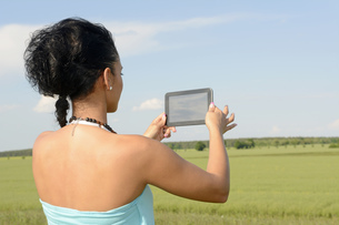 Young woman photographing with digital tablet, back viewの写真素材 [FYI04335390]