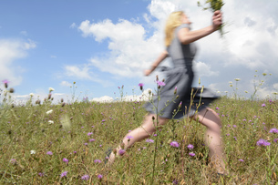 Young woman running on wildflower meadowの写真素材 [FYI04335391]