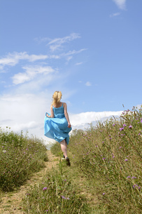 Young woman running on field pathの写真素材 [FYI04335393]