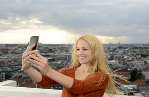 Germany, Berlin, young woman taking a selfie with her smartpの写真素材 [FYI04335404]