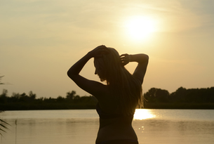 Germany, Brandenburg, silhouette of young woman in front ofの写真素材 [FYI04335405]