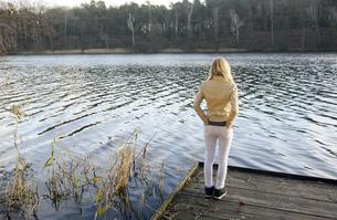 Back view of blond woman standing on wooden boardwalk lookinの写真素材 [FYI04335411]