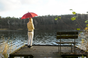 Back view of blond woman standing on wooden boardwalk with rの写真素材 [FYI04335413]