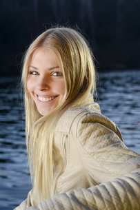Portrait of relaxed blond woman in front of a lakeの写真素材 [FYI04335416]