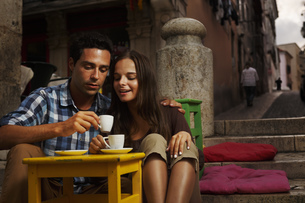 Portugal, Lisboa, Bairro Alto, young couple sitting at streeの写真素材 [FYI04335420]