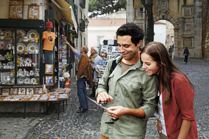 Portugal, Lisboa, Baixa, Rossio, young couple looking at posの写真素材 [FYI04335421]