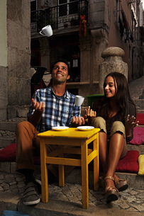 Portugal, Lisboa, Bairro Alto, young couple sitting at streeの写真素材 [FYI04335425]