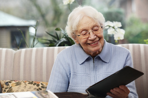 Smiling senior women watching old photographs at homeの写真素材 [FYI04335434]