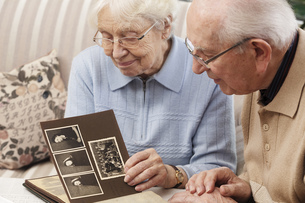 Senior couple watching old photograph album at homeの写真素材 [FYI04335436]