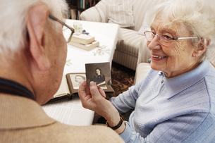 Senior woman showing her husband old photograph of herselfの写真素材 [FYI04335437]