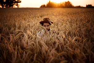 Man with hat hiding in corn fieldの写真素材 [FYI04335458]