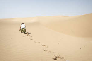 Man crawling on all fours alone in the desertの写真素材 [FYI04335463]