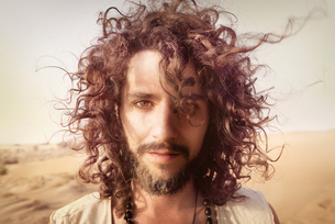 Portrait of man with beard and curly hair in the desertの写真素材 [FYI04335464]