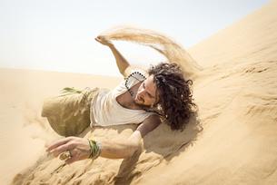 Man rolling down sand duneの写真素材 [FYI04335469]