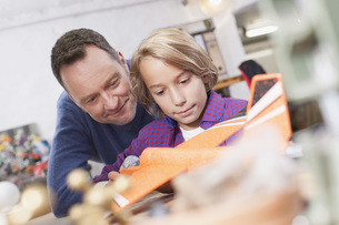 Germany, Leipzig, Father and son repairing toy planeの写真素材 [FYI04335478]