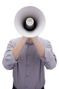 Young man holding megaphone in front of his faceの写真素材 [FYI04335502]