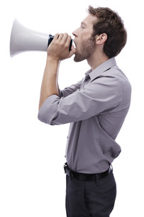 Young man holding megaphone, side view, portraitの写真素材 [FYI04335505]