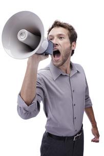 Young man holding megaphone, portraitの写真素材 [FYI04335508]