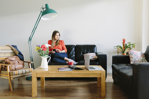 Young woman relaxing on the couch in her living roomの写真素材 [FYI04335511]