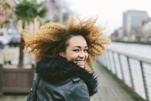 Ireland, Dublin, smiling woman with afro looking over her shの写真素材 [FYI04335512]