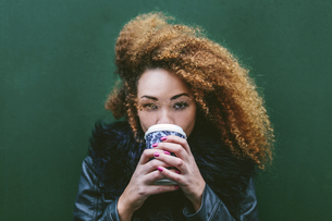 Portrait of woman drinking coffee to go in front of a greenの写真素材 [FYI04335515]