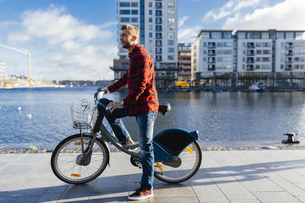 Ireland, Dublin, young man at city dock with city bikeの写真素材 [FYI04335518]