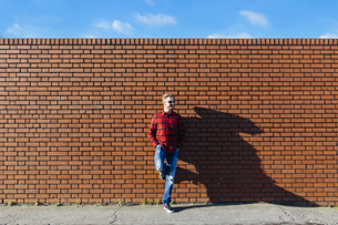 Young man leaning against brick wallの写真素材 [FYI04335520]