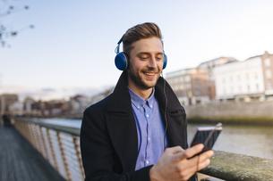 Ireland, Dublin, young man holding smartphone hearing musicの写真素材 [FYI04335524]