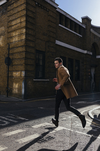 Young man in a hurry crossing urban streetの写真素材 [FYI04335530]