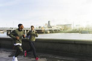 UK, London, man and woman running at riverwalkの写真素材 [FYI04335537]