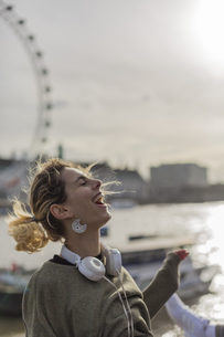 UK, London, laughing woman with headphones at River Thamesの写真素材 [FYI04335539]