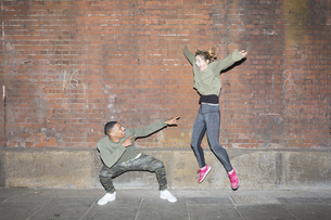 Playful young couple in front of brick wall at nightの写真素材 [FYI04335543]