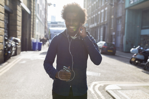 Young man listening to music from cell phone on urban streetの写真素材 [FYI04335544]