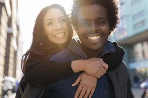 Happy young man carrying girlfriend piggybackの写真素材 [FYI04335546]